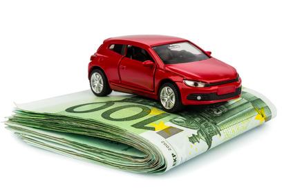 Ein Auto steht auf Euroscheinen. Kosten für Autokauf, Benzin, Versicherung und andere Autokosten